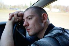 Un hombre joven triste se está sentando en el coche, inclinándose en el volante imagenes de archivo