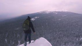 Un hombre joven, turista, se coloca al borde de una montaña nevada y admira el top de la montaña metrajes