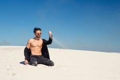 Un hombre joven vierte maravillosamente la arena con una mano fotografía de archivo