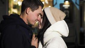 Un hombre joven y de la muchacha un beso, un abrazo y una sonrisa hermosos apasionado en uno a metrajes