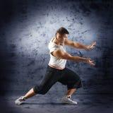 Un hombre joven y deportivo que hace una actitud de la danza moderna Fotografía de archivo
