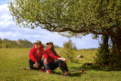 Un hombre joven y su muchacha con longboards están descansando cerca de un árbol Fotos de archivo libres de regalías