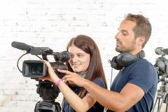Un hombre joven y una mujer con la cámara de vídeo profesional Imágenes de archivo libres de regalías