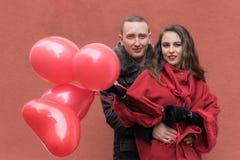 Un hombre joven y una mujer joven con los accesorios rojos a Imágenes de archivo libres de regalías