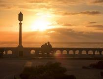 Un hombre joven y una mujer en el amor que se sienta en un banco en la costa y que disfruta de una puesta del sol hermosa fotos de archivo