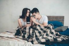 Un hombre joven y una mujer están bebiendo el café por la mañana en cama Mañana romántica en casa Fotografía de archivo