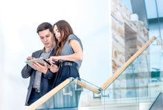 Un hombre joven y una mujer joven que se colocan en las escaleras Foto de archivo libre de regalías