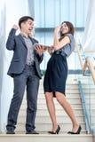 Un hombre joven y una mujer joven que se colocan en las escaleras Imágenes de archivo libres de regalías