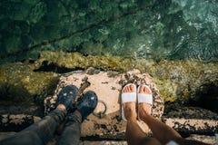 Un hombre joven y una mujer sus piernas junto sobre un embarcadero fotos de archivo libres de regalías
