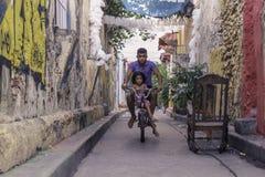 Un hombre joven y una niña que montan una bici en las calles de Cartagena foto de archivo libre de regalías