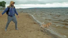 Un hombre juega con un perro por el r?o