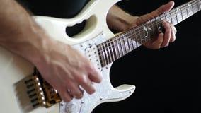 Un hombre juega a solas en una guitarra eléctrica blanca en un fondo negro Primer almacen de metraje de vídeo