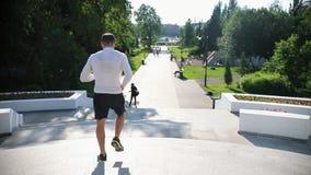 Un hombre juguetón que corre en las escaleras en el parque almacen de metraje de vídeo