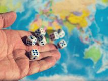 Un hombre lanza siete dados en el mapa del mundo El concepto de propiedad del mundo ORDEN MUNDIAL mapa y dinero de d Fotografía de archivo