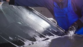 Un hombre lava el vidrio del coche Concepto de túnel de lavado manual metrajes