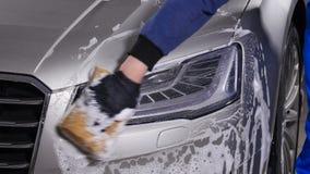 Un hombre lava las linternas del coche Concepto de túnel de lavado manual metrajes