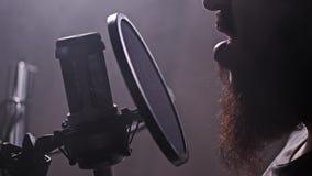 Un hombre lee el texto en un estudio de grabación Boca y micrófono del primer 4K MES lento metrajes
