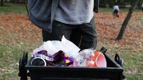 Un hombre limpia basura en un parque público El concepto de cuidar para el ambiente y de cuidar para el ambiente Parque del otoño almacen de video