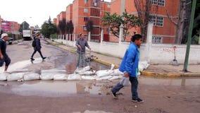 Un hombre lleva algunas bolsas de arena para proteger su calle debida la inundación