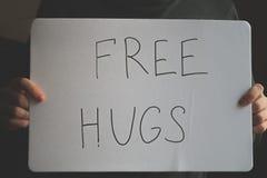 Un hombre lleva a cabo una nota con la inscripción - libere los abrazos Concepto del día de fiesta al día internacional de abrazo Foto de archivo libre de regalías