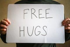 Un hombre lleva a cabo una nota con la inscripción - libere los abrazos Concepto del día de fiesta al día internacional de abrazo Imagen de archivo