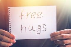 Un hombre lleva a cabo una nota con la inscripción - libere los abrazos Concepto del día de fiesta al día internacional de abrazo Foto de archivo