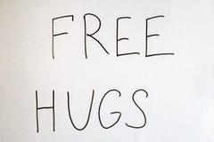 Un hombre lleva a cabo una nota con la inscripción - libere los abrazos Concepto del día de fiesta al día internacional de abrazo Fotografía de archivo