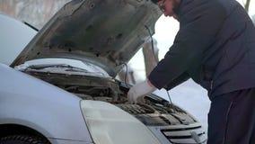 Un hombre lleva un hogar de la batería de coche Es exterior muy frío almacen de metraje de vídeo