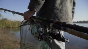 Un hombre lleva las cañas de pescar y las redes se cierran para arriba Cámara lenta almacen de video