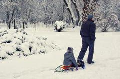 Un hombre lleva a un niño en un trineo Invierno en el parque Imagen de archivo libre de regalías