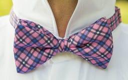 Un hombre lleva una corbata de lazo rosada a cuadros Imagen de archivo