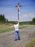 Un hombre lleva una cruz imagenes de archivo