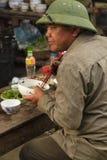 Un hombre, llevando un sombrero, toma su desayuno en Bac Ha Imágenes de archivo libres de regalías
