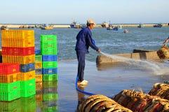 Un hombre local está limpiando sus cestas que fueron utilizadas para transportar pescados del barco al camión Fotos de archivo libres de regalías