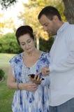 Un hombre más joven que ayuda a la mujer mayor con su teléfono elegante Fotografía de archivo libre de regalías