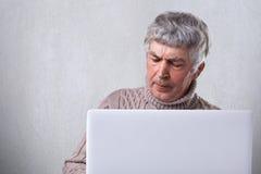 Un hombre maduro con la localización gris del pelo delante de su ordenador portátil que descontenta la expresión y arrugas en su  Foto de archivo