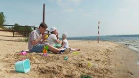 Un hombre maduro en una camisa de tela escocesa con dos muchachas se está sentando en la arena por el río Actividades al aire lib almacen de metraje de vídeo