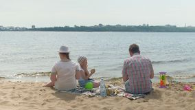Un hombre maduro en una camisa de tela escocesa con dos muchachas se est? sentando en la arena por el r?o Actividades al aire lib almacen de metraje de vídeo