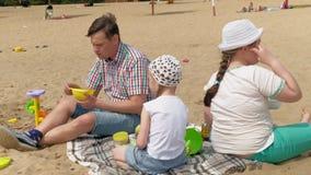Un hombre maduro en una camisa de tela escocesa con dos muchachas se est? sentando en la arena por el r?o Actividades al aire lib metrajes