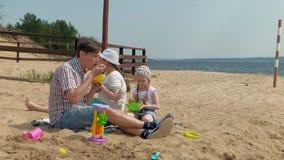 Un hombre maduro en una camisa de tela escocesa con dos muchachas se est? sentando en la arena por el r?o Actividades al aire lib almacen de video