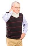 Un hombre maduro herido con el tenedor del cuello que sufre de un dolor Imágenes de archivo libres de regalías