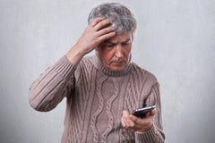 Un hombre maduro preocupado que lleva a cabo su mano en su cabeza gris mientras que usa el smartphone que lee un ciertas noticias foto de archivo