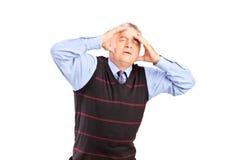 Un hombre maduro que lleva a cabo su cabeza en dolor Imagen de archivo libre de regalías
