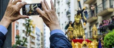 Un hombre mantiene en su teléfono móvil la imagen del paso de la procesión de Jesús el Nazarene Huelva, España imagen de archivo libre de regalías