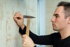 Un hombre martilla un clavo en la pared del yeso debajo del papel pintado fotos de archivo libres de regalías