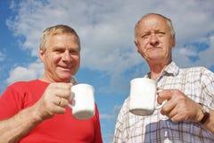 Un hombre mayor bebe té en la naturaleza Fotos de archivo libres de regalías