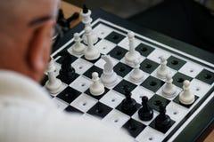 Un hombre mayor con los vidrios juega al ajedrez especial para las persianas fotografía de archivo