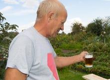 Un hombre mayor con placer y placer está bebiendo la cerveza fría de una taza en un fondo de árboles en su jardín Imágenes de archivo libres de regalías