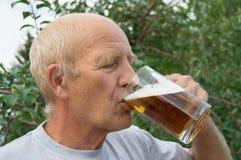 Un hombre mayor con placer y placer está bebiendo la cerveza fría de una taza en un fondo de árboles en su jardín Foto de archivo libre de regalías