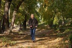 Un hombre mayor corre a lo largo de la trayectoria en el bosque Foto de archivo libre de regalías